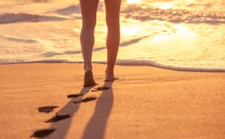 Relaxing beach holiday. Girl walking on the beach at sunset.