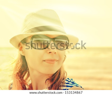Relaxing beach woman enjoying the summer sun happy in a cap and sunglasses