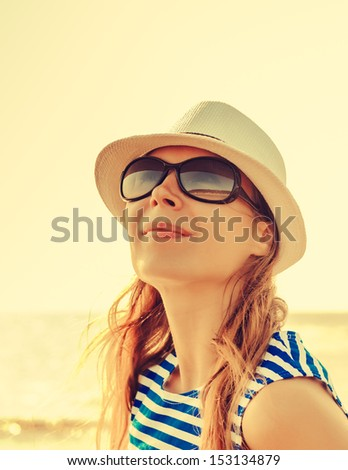 Relaxing beach woman enjoying the summer sun happy in a cap and sunglasses with face raised to the sunlight.