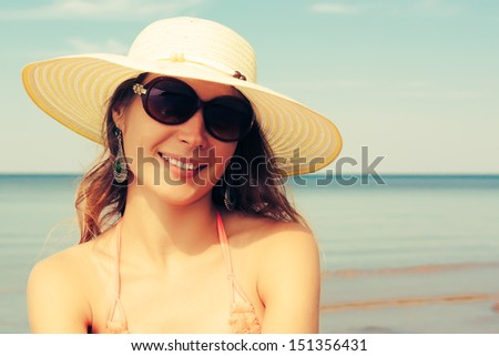 Relaxing beach woman enjoying the summer sun happy in a wide sun hat and sunglasses at the beach