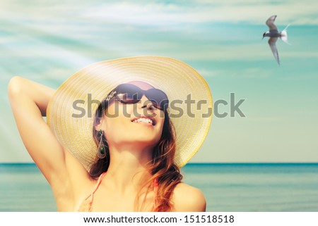 Relaxing beach woman enjoying the summer sun happy in a wide sun hat at the beach with face raised to the sunlight.
