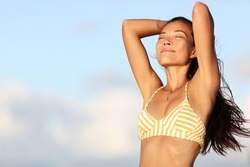 Relaxing bikini woman feeling good and free in outdoor nature breathing fresh air with arms up showing healthy body and smooth skin and armpits for laser epilation treatment. Asian model on beach.