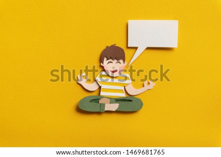 Relaxing boy sitting in lotus pose and meditating. Concentrated man with empty speech bubble. Yoga concept. Hand cut paper illustration on yellow background