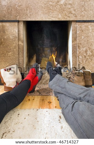 Relaxing by the fireplace - two pairs of feet warming near the fire after a long, cold, winter hike