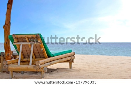 Relaxing Chair on white sandy Beach looking toward ocean and blue sky