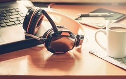 Relaxing concept by listening to music in the office. The music headphones that are placed next to the laptop computer, along with the hot coffee in a white cup on a wooden desk in the workplace.