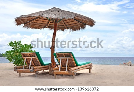 Relaxing couch chairs with bamboo parasol on white sandy Beach looking towards ocean and blue sky