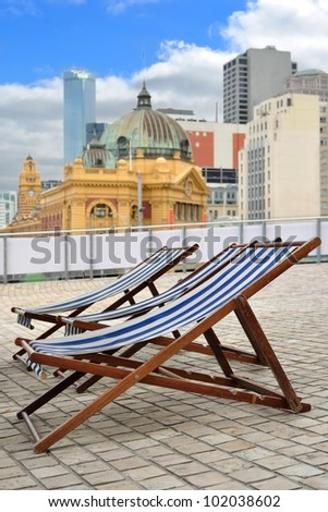 Relaxing deck-chairs in center of city, Melbourne icon Flinders Street station in background, Australia