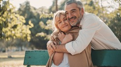 Relaxing,family,free time,age,tourism,travel and people concept.Senior couple hugging and Happy mature people in winter clothes embracing on bench.Elderly couple sitting on bench in autumn park.