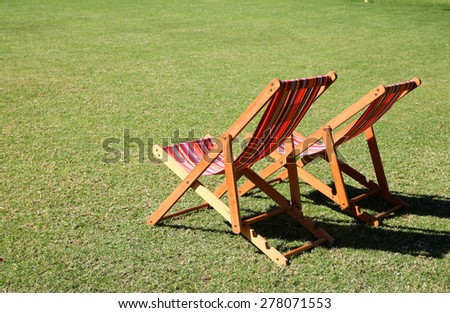 Relaxing garden chairs in garden setting surrounded by grass