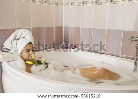 Relaxing in bathtub with candles and flowers - stock photo