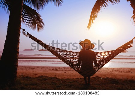relaxing in hammock at sunset on the paradise beach