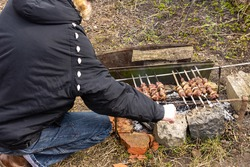 Relaxing in the garden in nature, juicy wild goat kebabs on skewers, a hunter's trophy, cooking kebabs on a fire, the man turns the kebabs on the fire