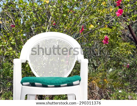 Relaxing in the garden with white plastic patio chair. Front view of outdoor garden chair with green cloth seat cusion. Foliage and flower background.