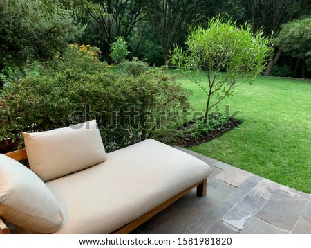 Relaxing lounge chair outdoors in green peaceful tranquil garden