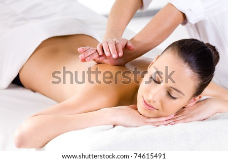 Relaxing massage for young beautiful woman in the spa salon - horizontal - stock photo