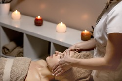 Relaxing massage. Woman receiving head massage at spa salon, side view.