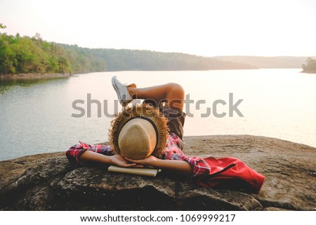 Relaxing moments, Asian young boy relaxing outdoor on the lake in sunset. Relax time on holiday concept travel. Hipster tone style. #1069999217