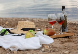 Relaxing on a sandy beach. background with fruit, hat, glasses of red wine on the beach, by the sea or ocean .Romantic picnic for couple on the beach at sunset.