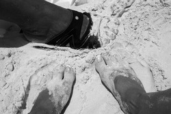 Relaxing on the beach and burying feet in the sand