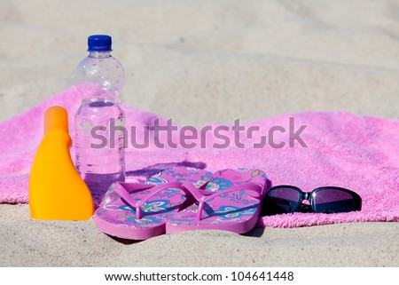 Relaxing on the beach with sun cream and bottle of water
