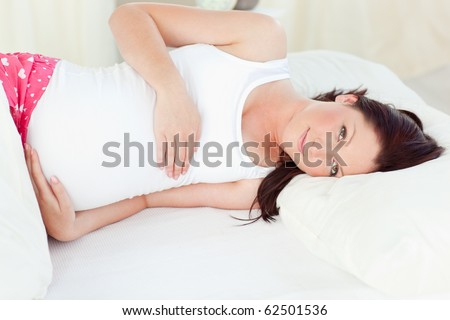 Relaxing pregnant woman sleeping in her bed at home