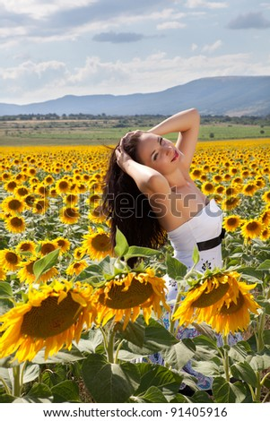 Relaxing pretty woman in a yellow bulgarian sunflower field