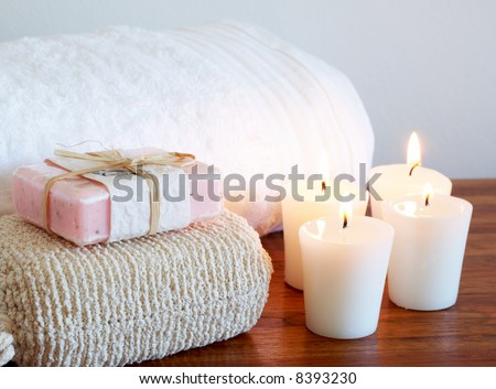 Relaxing spa scene with white fluffy towel, body sponge and handmade soap with candles in the background
