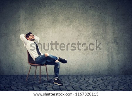 Relaxing stylish business man in glasses sitting on chair with hands behind head on gray background #1167320113