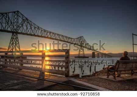Relaxing sunset behind the bridge - stock photo
