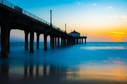Relaxing sunset view with tall concrete pillars under beach pier and silky ocean water below. Peaceful outdoor scene; concept of freedom.