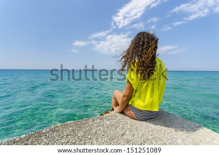 Relaxing teenage girl. Curly hair young woman is enjoy calm ocean water surface and clear sky and horizon at bahamas.