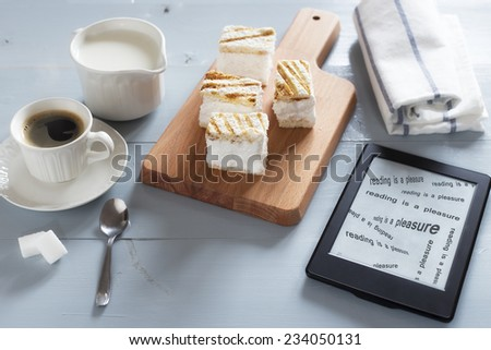 Relaxing time with literature, hot beverage and desserts. E-book reader on a wooden table with text READING IS A PLEASURE written on the screen. Also a cup of hot coffee, milk and sweets on wood tray