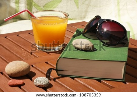relaxing utensils in summer: book, sun glasses and juice