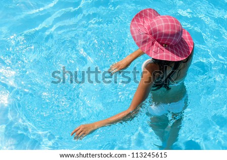 Relaxing woman in pool on summer holiday.  Caucasian woman relaxing into water, Copy space.
