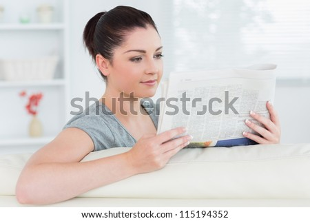Relaxing woman sitting on the couch in a living room and reading a newspaper