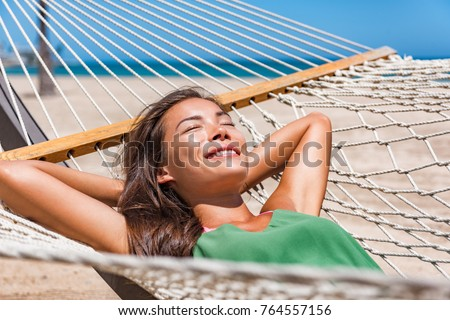 Relaxing woman sleeping on hammock in the tropical sun. Asian girl resting lying down in resort lounger laid back enjoying suntan in Caribbean travel holidays.