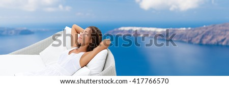 Relaxing woman sleeping on outdoor daybed patio furniture enjoying view of Mediterranean sea Europe travel destination. Asian girl lying down on pillows dreaming carefree happy. Luxury home living.