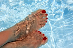 Relaxing woman with his foot on the water