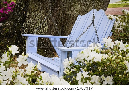 Relaxing wooden blue swing with azaleas in the Southern USA