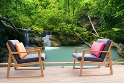 relaxing wooden desk on wood terrace against beautiful waterfalls in deep forest use for relax time in pure nature and refreshing time