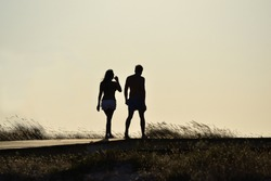 Relaxing young couple silhouette. Man and woman walking by a pathway on a beach.