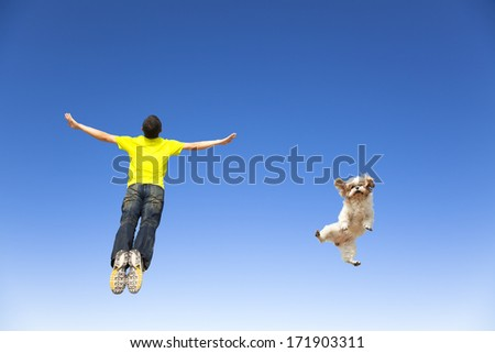 relaxing young man and  dog jumping in the sky