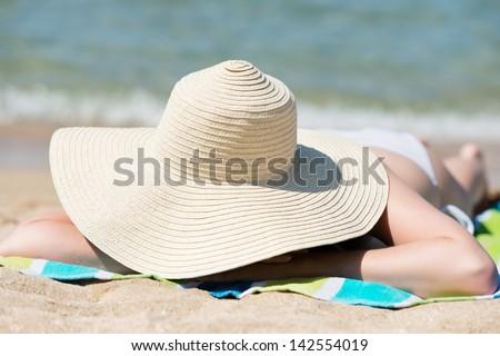 Relaxing young woman with sunhat enjoying the sun at beach