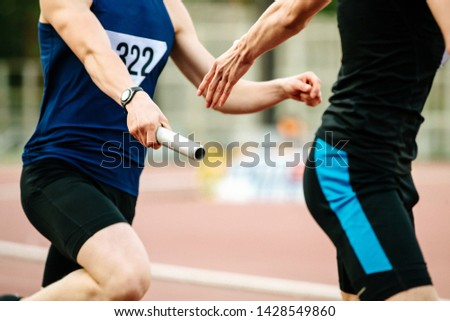 relay race men athletes runners passing baton competition in athletics