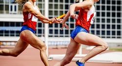 relay race passing of baton women athletes runners