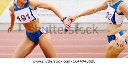 relay race passing of baton women relay team in athletics Foto d'archivio ©