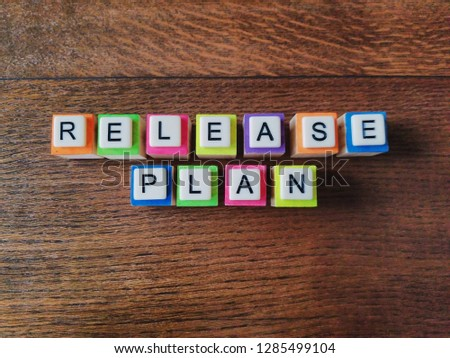 Release Plan text colorful letters on wood background, flat layout #1285499104