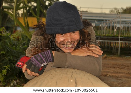 Relent the real skin of the farmer Thai, Asian women aged 50 years hold the smartphone in hand and smile authentic. Dressed like a soldier, laying relax, smiling happily on a log, blurred background . Stock fotó ©