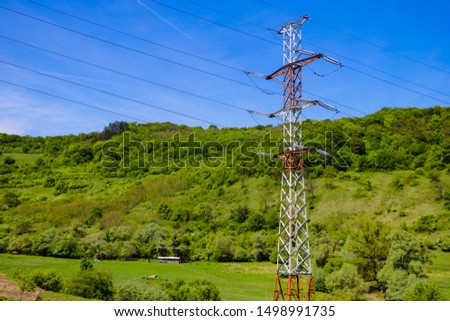 Reliance of high voltage power lines and blue sky on a background of green mountains.
